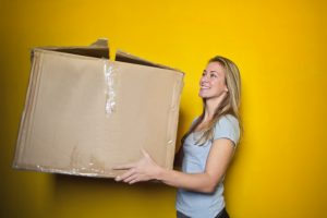 A woman is holding a large carton box. - something our Long Island movers can help you with