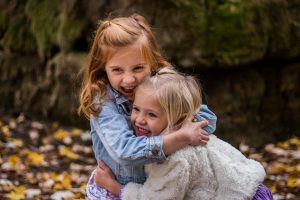 A pair of adorable, hugging girls standing in nature. Do you want your children to love the outdoors like that? Ring your movers Westchester County today.