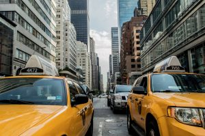 Two yellow cabs in a traffic jam in NYC.