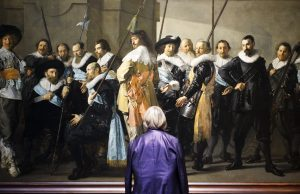 a man standing in front of the painting