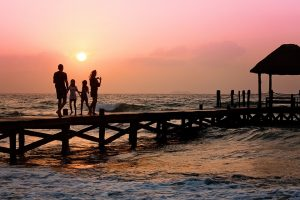 A family on a pier during sunset.