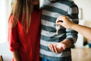 A man and a woman receiving a house key. The woman is wearing a red sweater, the man is wearing a hoodie with green stripes.
