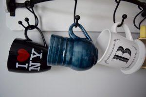 A mug with I HEART NY on it on a rack with several mugs.
