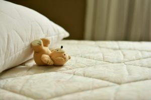 A teddy bear on the bed.