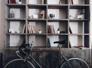 Shelves with books on them and a bike