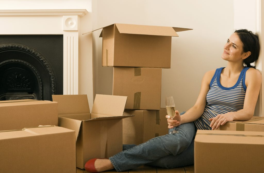 a woman sitting among cardboard boxes with a glass of champagne