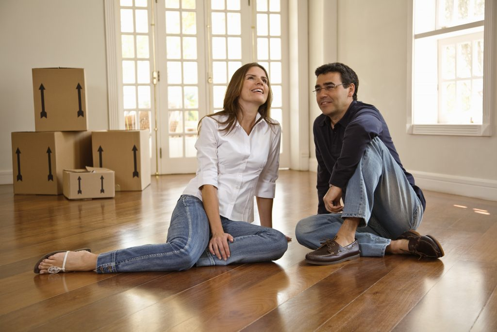 Couple sitting in new home, representing the services of movers in Richmond Hill NY
